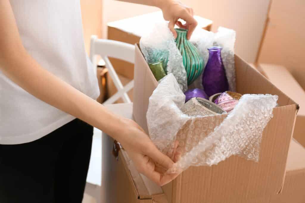 mujer desembalando caja con productos menaje